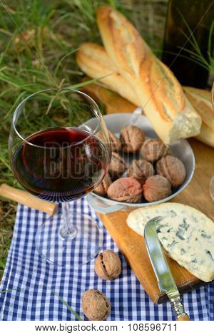 Picnic concept - Wine, delicious cheese, walnuts and baguette on wooden board, outdoors