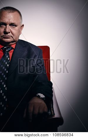 Portrait of serious middle aged businessman wearing black suit, red shirt and wristwatch sitting on old fashioned sofa in office