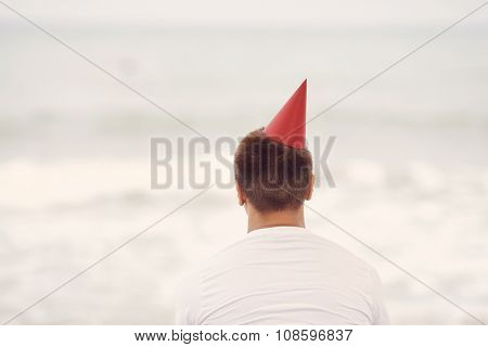 Retro colored back view portrait of young man wearing red party hat and white t-shirt celebrating birthday sitting alone on beach near tropical sea - loneliness concept