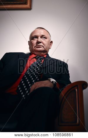 Serious middle aged businessman wearing black suit, red shirt and wristwatch sitting on old fashioned sofa in office and looking aside