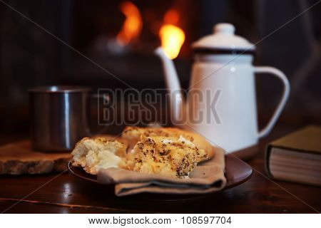 Teapot and mugs on vintage wooden table. Fireplace as background
