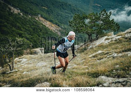 middle-aged man with walking sticks going uphill