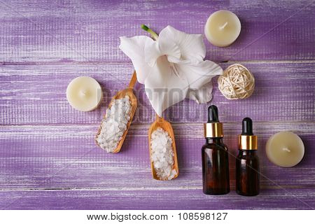 Spa composition of candles, oil, sea salt and flower on purple wooden background