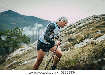 middle-aged man with walking sticks is on side of mountain