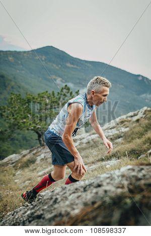male athlete senior years climbing mountain to mountainside