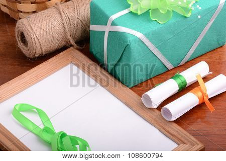 Blank Photo Frame With Christmas Gift Box, White Paper With Bow On Wooden Table.