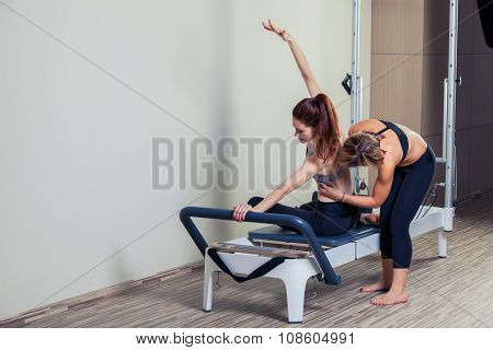 Pilates reformer workout exercises man with instructor  at gym indoor