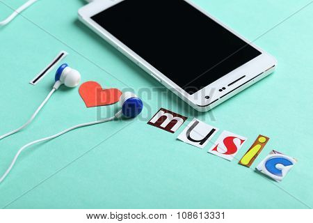 White Smartphone With Earphones On Mint Paper Background