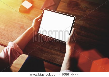 Young hipster guy working on touch pad while sitting at wooden table