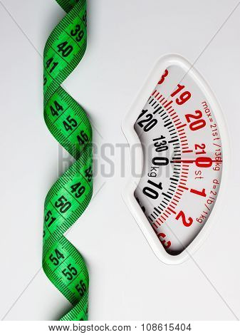 Green Measuring Tape On Weight Scale. Dieting