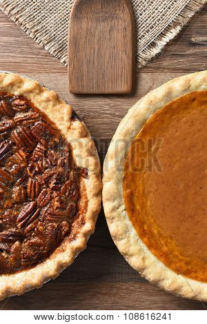 High angle vertical of half of a Pecan Pie and a Pumpkin Pie. The fresh baked pies are on a wood table with burlap table cloth and wood utensil.