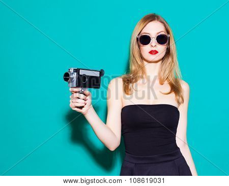 Beautiful Fashionable Girl Posing And Holding A Vintage Movie Camera In Black Dress And Sunglasses O