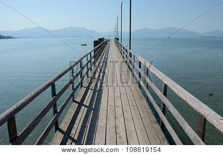 Long Wooden Pier At Chiemsee Lake In Germany