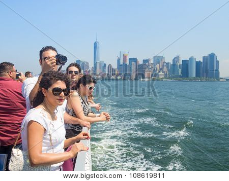 NEW YORK,USA - AUGUST 16,2015 : Tourists in a cruise ship on the bay of New York with the Manhattan skyline on the background