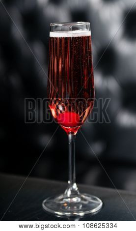 Red cocktail served on a black table