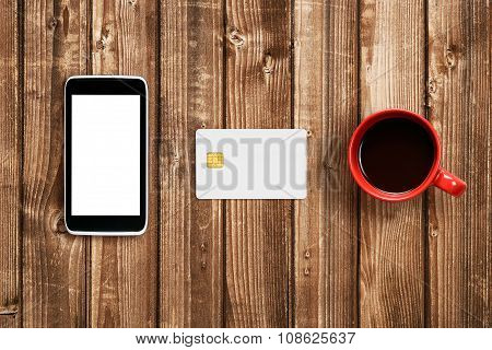 Plastic Card, Smartphone And Coffee Cup On Wooden Table