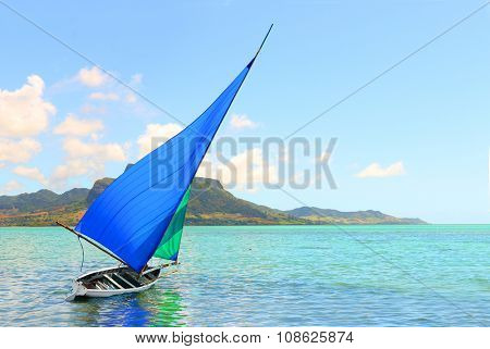 Sailboat in Mahebourg bay with Morne Brabant on background. Mauritius island.