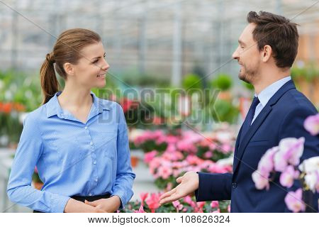 Pleasant businesspeople talking in the greenhouse