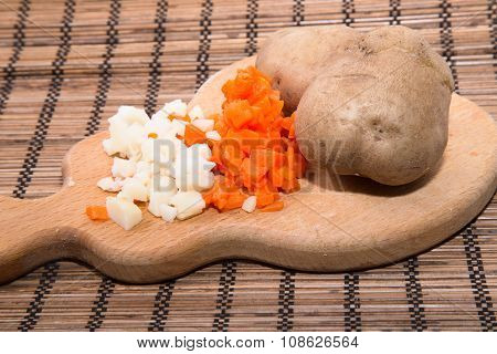 Small Cut Boiled Carrots, Boiled Potato In A Peel And Cut, On A Figured Wooden Board
