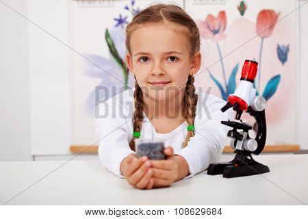 Young girl in biology class holding seedling