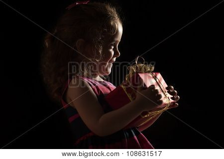 Winter, Holidays, Christmas Concept - Silhouette Of A Beautiful Little Girl With Gift Box Over Black