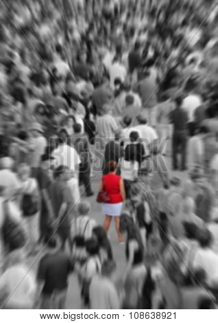 Blur background showing woman in red in a middle of a crowd in black and white