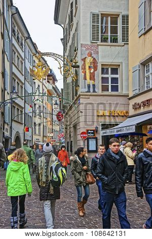 LUCERNE SWITZERLAND - JANUARY 04 2015: Crowded street of Lucerne with the house where Wolfgang von Goethe stayed during his visit to Lucerne and a bronze lantern in the form of double-headed eagle