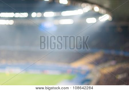 Blurred crowded football stadium with field, stands and spectators. 2016 sport background