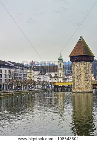 Water tower of a famous Chapel Bridge in Lucerne. Jesuit church seen in the background. Switzerland. Europe.