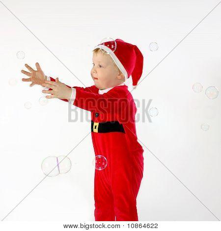 Kleiner Junge versucht, einige Seifenblasen fangen