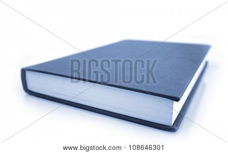 Closed book on plain background