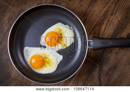 frying eggs in pan on wooden table