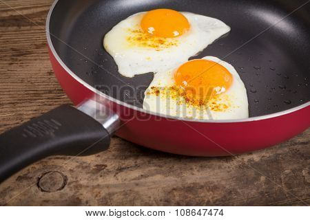 frying eggs in pan on old table