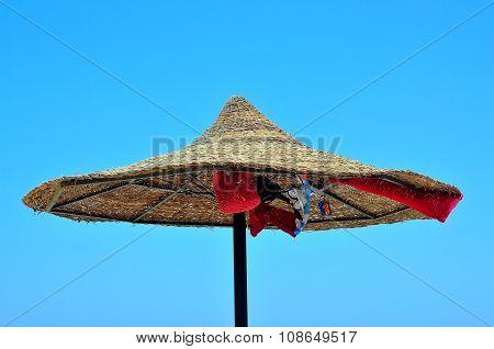 straw beach umbrella in the blue sky