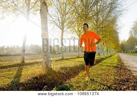 Young Sport Man Running Outdoors In Off Road Trail Ground With Trees