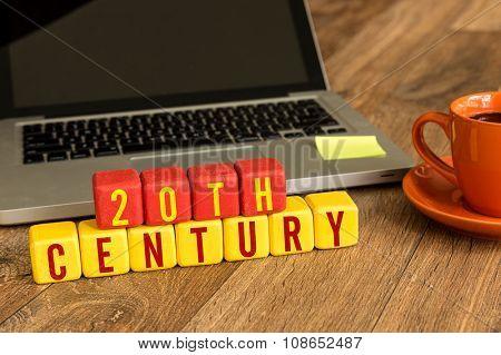 20th Century written on a wooden cube in a office desk