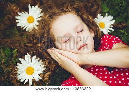 Sweet Little Girl Sleeping On The Grass With Chamomiles.