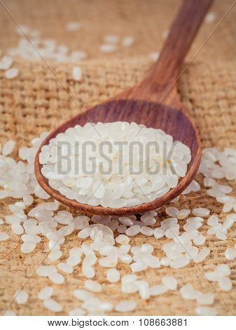 Whole Grain Traditional Japanese Rice  In Wooden Spoon With Hemp Sacks Background