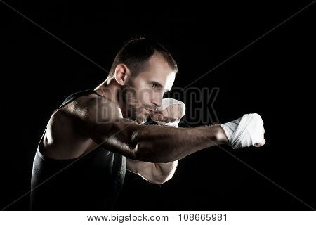 muscular man, tying an elastic bandage on his hand, black background