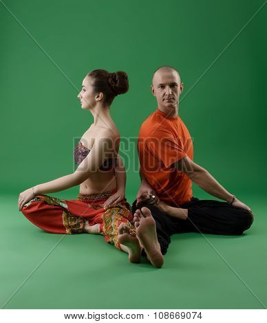 Man and woman doing yoga in pair. Studio photo