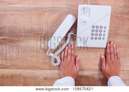 Businesswoman holding a phone at her desk at work