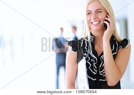 Beautiful businesswoman using cell phone , standing in office