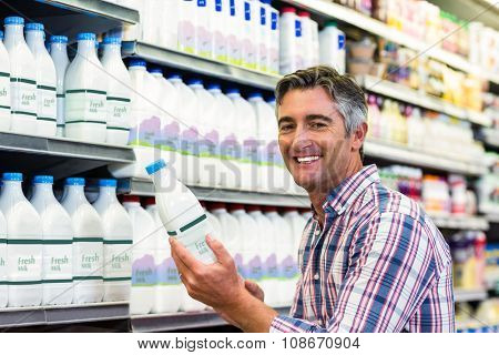 Man holding milk bottle in the supermarket and smiling at the camera