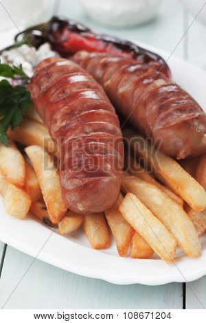 Grilled german sausages with french fries and roasted peppers