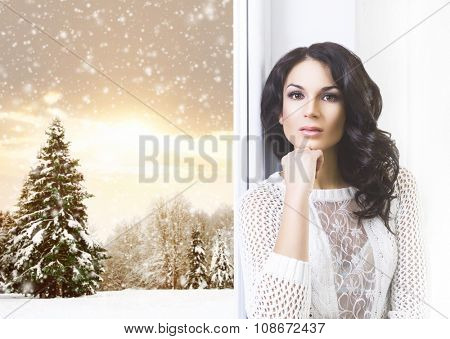 Young and beautiful brunette woman posing near the window with a view of snowy conifer tree and sunset.