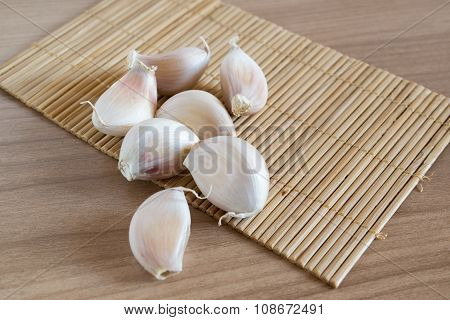 Garlic Cloves On Makisu Mat On Wood Texture