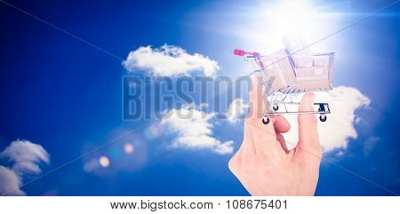 Hand showing house against bright blue sky with clouds