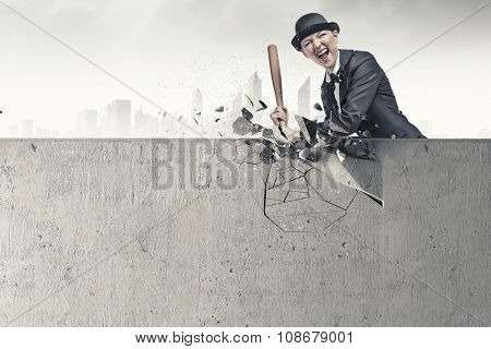 Young pretty woman in suit and hat crashing wall with baseball bat