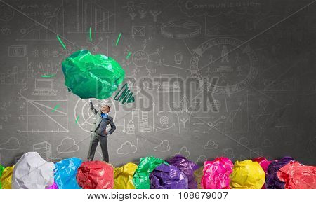 Businessman lifting in hand big crumpled ball of colorful paper as creativity sign