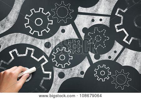 Businessman hand drawing with chalk gears mechanism as teamwork concept